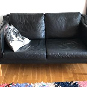 Flot, retro 2 pers. Mogens Hansen lignende sofa i sort læder. Brugt, men ingen skader. Læderet er begyndt at få flot patina  Sælges grundet flytning. Flere billeder kan sendes.     L: 140 cm  H: 50 cm + 20 cm ben  D: 75 cm   Siddehøjde 37 cm  Er på Øbro