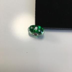 """Eksklusiv Troldekugle """"The Diamond Bead"""". 13 zirkoner er indstøbt i krystal på en baggrund af smaragdgrønt glas (design Lise Aagaard). Skinner meget flot, men jeg har kun båret den 2 gange i en halskæde."""