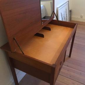 Lille skrivebord i teaktræ. Perfekt til studieværelset, det lille kontor eller børneværelset. Bordet har et rum under bordpladen med lille spejl - genialt makeup værksted. Flot stand.  Mål:  Bredde = 105cm.  Højde = 73cm.  Dybde = 60cm.
