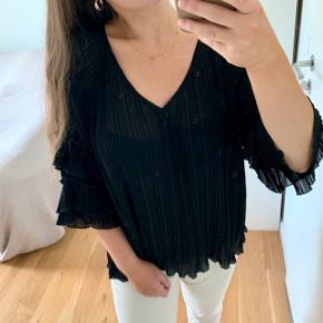 Sød og luftig bluse med flæser. Går både med bukser og nederdele.