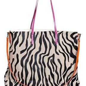 Super skøn taske med sorte zebra-striber fra det danske mærke By Malene Birger. Modellen er med både håndtag og skulder-stropper, hvor håndtaget er lavet i en pink farve og skulder-stroppen i orange. Modellen er med fast bund og har en skøn, oversize størrelse, så den kan bruges til lidt af hvert. Indeni tasken er der et stort rum samt to små. Tasken kommer med dustbag.