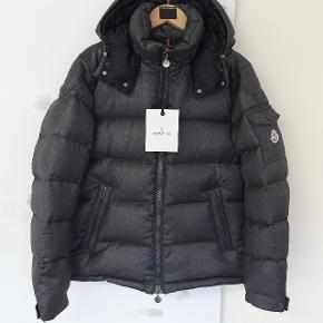 MONCLER MONTGENEVRE DARK GRAY PADDED str. S   Jacket in lightweight carded flannel lined in nylon with down padding Detachable hood with enamelled tone-on-tone press-studs Front die-cast zip fastening Pocket on left sleeve with enamelled tone-on-tone press-studs Elastic drawstring in the hood and bottom hem Cloth Moncler badge on left sleeve Short length  Composition: Lining: Feather Down 100%, Polyamide 100% Outer: Wool 100%  Washing instructions:dry clean only  100 % ægte