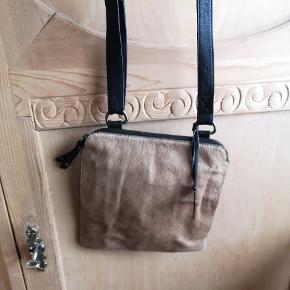 Depeche crossbody taske med pels front 😍 Tasken er stort set ikke brugt og ser ud som ny 😊 Den har et stort rum, et til en mobil og 4 rum til kort samt et lille lynlås rum inde i tasken. På bagsiden er der 2 lynlås rum med god plads. Tasken er 23,5 cm bred og 25,5 cm høj. Sælges for 125 kr. plus forsendelse.