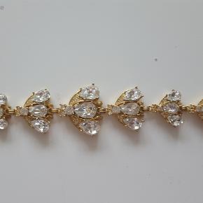 Smykkesæt fra Christian Dior  Christian Dior smykkesæt bestående af armbånd og broche af gyldent metal i form af bier, hver prydet med talrige facetslebne klare sten. L. 19 og 5 cm. (2)  Stand: En lille bi i armbåndet mangler en dråbe facetslebet sten.  Sælges samlet