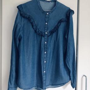 """Denim skjorte fra Only str. 42 i mørkeblå.  Skjorte har fine flæser hele vejen rundt og er med trykknapper. Skjorten er normal i størrelsen og ikke en oversize model men normal """"lige op og ned"""".   Jeg tager ikke billeder med tøjet på, da jeg ikke kan passe det mere.  Mvh. Katrine"""