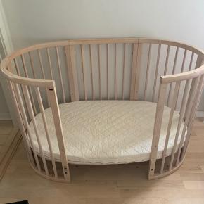 """Stokke Sleepi tremmeseng som kan bruges fra baby til stor. . På billedet er den juniorseng. Der medfølger ekstra 2 plader der bruges som bund i den korte udgave. Samt ekstra side.  Madras til begge størrelser medfølger.  Bunden kan løftes når barnet er lille. Så den kommer op i """"arbejdshøjde"""". Ligeledes kan sengen skilles til to stole når barnet ikke bruger den som seng længere.  Der medfølger original rulleskuffe der kan bruges til opbevaring og skubbes under sengen.  Sengen står rigtig pæn og har en nypris med alle dele på 7895,- Der er små brugsspor på madrasserne, ikke meget. Selvfølgelig er der også små spor på sengen men ingen store ridser og hakker.  Virkelig lækker seng."""