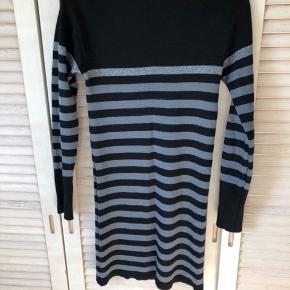 Smuk og lækker kjole i blød uld fra Mads Nørgaard. Stribet grå og sort med en enkelt sølv stribe. Ingen fnuller. Tætsiddende.
