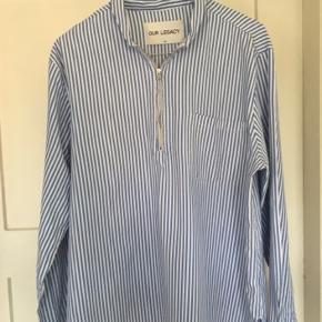 Rigtig fed lyseblå og hvid stribet skjorte fra Our Legacy. Næsten som ny, med ingen tegn på slitage eller lignende. Sælges, da jeg desværre ikke kan passe skjorten længere. Nypris: 1500 ,-  BYD!