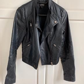 Faux læder jakke fra Topshop størrelse 36. Ingen tydelige brugsspor på ydersiden, men foret er gået i stykker i det ene ærme indeni. Har ingen betydning for udseendet.