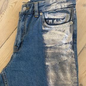 Fede jeans fra H&M med sølv stribe på hvert ben samt rå afslutning ved anklerne