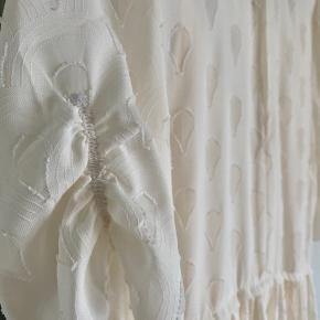 Næsten ny kjole fra H&M str. 36. Kjolen har et loose-fit, lukkes foran og med pufærmer. Kjolen er lidt creme i farven og derfor ikke helt hvid.
