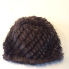 Minkhue. Mørkebrun. Den har en klassisk rund facon og er elastisk.  Nypris 950 kr.