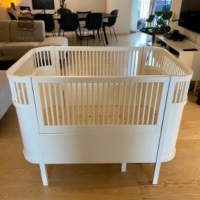Sebra Kili / Juno seng til baby & junior  Utrolig god stand med meget få brugsspor.  Det er den nye model, hvor bunden er justerbar og kan hæves/sænkes.  Madrasser medfølger.   Sengen sælges samlet.  Nypris for seng 5.795,- Nypris for madrasser 1.195,-  Sælges for 4.000,-  Flere billeder kan sendes.
