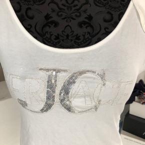 Smart T-shirt med palietter foran. Detalje med knap på bagsiden. Bindebånd over Venstre skulder.  Brugt få gange.  Forsendelse med DAO Kr. 38.- betales af køber.    #30dayssellout