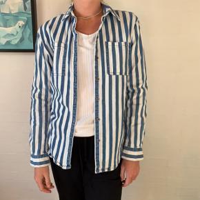 Blå og hvid denim skjorte. Brugt en eller to gange og kun vasket én gang.  Lidt lille i størrelsen