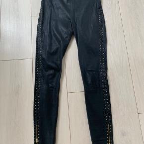 Fede sorte ægte skind-leggings med nitter ned langs siderne , lukkes med lynlås i siden. Lynlåse ved buksebenene...  Ægte skind  Brugt 1 gang , meget fin stand, mindstepris 625 kr