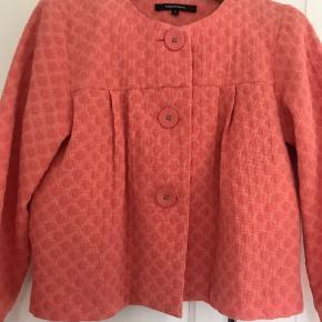 Coralfarvet kort jakke.
