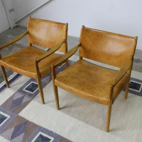 Et par lænestole af Per Olof Scotte i eg og cognac farvet kernelæder. Model premiär 69, Vintage IKEA. Står i flot stand.  Pris 4750,- stk.  Kan leveres i hele landet. Retro. Skandinavisk design. Armstol. Karin mobring.