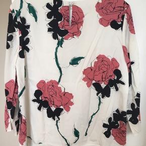 Super lækker silkebluse med blomsterprint fra det luksuriøse britiske mærke Jaeger / Jæger. Den har et let a-snit med læg samt bådudskæring og lidt vidde på ærmerne. Det er et helt utrolig klædelig snit og kvaliteten må silken er kraftig - kvaliteten kan virkelig mærkes. Den er foret så man kan ikke se igennem den. 95% silke og 5% elastan. Farverne er hvid, sort, grøn og mørk rosa. Str. 40. Kom med et bud. NP: 1500kr.   Varen befinder sig i 9520 Skørping. Sender med DAO.  Se også min øvrige annoncer. Jeg sælger tøj, sko og accessories. Pt er min shop fuld af vintagekup, high street fund og mærkevarer i mange forskellige str. Kig forbi og spøg endelig!