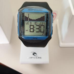 Helt nyt, aldrig brugt. Lækkert ur fra Rip Curl modelnavn s15 rifles tide watch A1119, farve Strong Blue.  FEATURES  Module Features:  500 Pre Programmed tide locations  100% Waterproof Tested  Quick view tide graph  Detailed Tide View  Future Tide  Alarm, Countdown Timer, Stopwatch and Light  Versatile tide display, Graph View or Detailed view