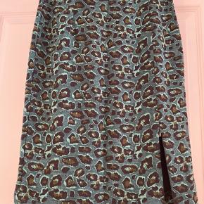 Smuk flaskegrøn nederdel i leopard print.  Nederdelen er kropsnær i en blanding af polyester/viskose/elestan