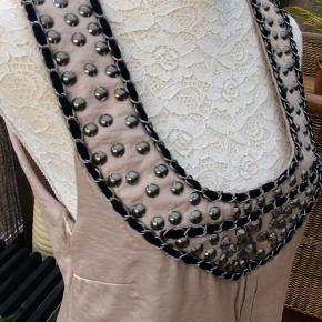 Kjolen er str. 40 - helt ny og ubrugt. Den er lavet i polyester og viskose. Der er lynlås i siden og kjolen har et tyndt underskørt.