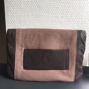 Fin clutch fra InWear i rosa/brun læder. Tasken har en udvendig lomme + indvendig lomme med lynlås. Tasken har aldrig været brugt og fremstår ny.