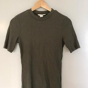 Armygrøn tætsiddende t-shirt med trekvartærmer sælges.  Skriv endelig, hvis du har spørgsmål.  Prisen er ikke fast, så kom gerne med et bud! 😊  Køber betaler fragten.  Mængderabat ved køb af flere af mine ting