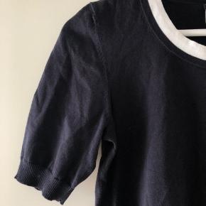 Den fineste bluse fra Chanel i bomuld. Fin rib detalje ved ærmer og i bunden der gør den kan sætte som man ønsker, tætsiddende eller lidt så den poser. Fin CC logo på overarmen, og rigtig god pasform, Kan også passe en m 😊  Bytter ikke!