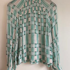 Sød bluse i hvid og grøn, med elastik detaljer ved hals og håndled. Stoffet er tynd og lidt gennemsigtigt. Mønstret er skævt foran(se billede)