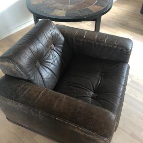Ultra behagelig læderlænestol sælges billigt.  En rigtig 'flyder' lænestol, i en rigtig lækker læderkvalitet (100% læder). Den sælges idet ejeren skal flytte i mindre bolig og desværre ikke har plads til den.  Denne læderlænestol er ca. 30 år gammel, og har derfor nogle uundgåelige slidmærker i lædere. Idet solen har ramt den har den fået en revne, som desværre har forårsaget en revne i læderet. Denne kan ses på billedet. Derudover fejler den absolut intet, og det er en god lænestol til at slå sig ned i efter en lang dag, eller blot til at sidde og læse eller se fjernsyn.  Mål: Bredde: 95 cm Dybde: 85  Højde: 68 cm  Hentes selv i Thisted, Nordjylland :)
