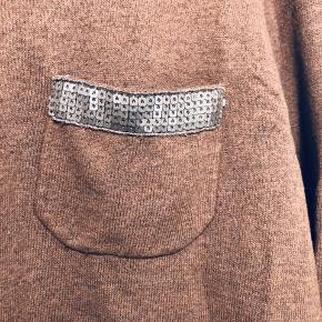 Fin strik med pailletdetalje på lommen samt lapper på albuerne. Der trekvart ærmer. Mine initialer står på mærket i nakken, hvorfor prisen er lav.  Køber betaler porto. Jeg tager ikke mål.