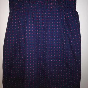 Sød kortere nederdel mørkeblå med rødeprikker.  Den har et tyndt for og falder pænt.