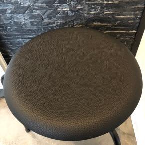 Står med nypolstret sæde i sort kunstlæder.