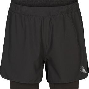 Trendsales har gratis forsendelse i efterårsferien 😀  Helt nye træningsshorts fra Zizzi, str XL (54/56), i sort. Stadig med tags. Har kun været ude ad posen for at tage billeder.   Har en del nyt Active by Zizzi i str 54/56, ikke alt er kommet op endnu.   Shorts fra Active by Zizzi.  Disse shorts er designet i 2 lag. Det inderste lag er tætsiddende og giver en god svedtransport. Det yderste lag er let  og sørger for god ventilation. Shortsene har en bred og blød elastik i livet, som sikrer en naturlig pasform, der følger din figur.
