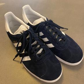 Adidas Gazelle sneakers. Brugt 2 gange. Sælges da de desværre ikke bliver brugt. Flot mørkeblå farve. Nypris er ca. 750 kr. Sælges for 400 kr. Kan afhentes i Charlottenlund.