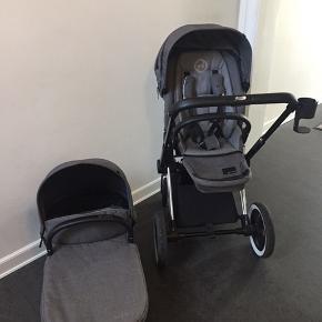 Cybex priam kombivogn sælges. Klapvogn (Lux Seat), stel, barnevognskasse, kopholder, regnslag og myggenet medfølger. Klapvognsdelen er Lux Seat, der kan ligges helt ned. Drejbare hjul, der kan låses fast. Stellet kan foldes helt sammen. Farven er Manhattan grey.