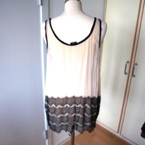 Smuk silketop med sort blonde. Meget rørlig vidde så kan bruges af både M og L  har lidt brugsspor ved hals  mål: bryst: 52cm længde: 71cm