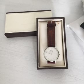 Sælger mit flotte Daniel Wellington ur da jeg ikke længere får det brugt. Det har en lille ridse i skiven som det des på andet billede, men det er ikke noget man ser når uret bruges. Ud over en læderrem følger også en blå og hvid stribet rem. Begge remme bærer præg af at de har været brugt, men til trods for dette er begge stadig pæne