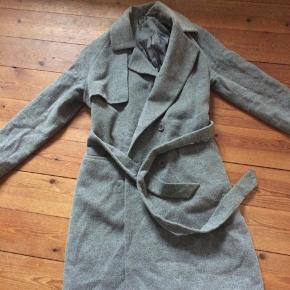 Se nærbilleder for standen på frakken og stoffet tæt på.
