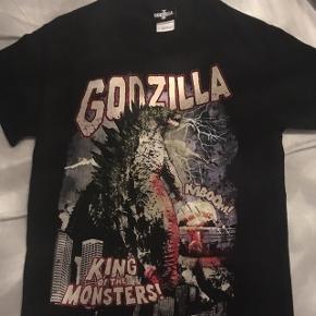 """Super fed """"Godzilla"""" t-shirt i sort med print. Str S, normal i størrelsen.   Nypris omkring 150 kr.  Hvis den skal sendes, betaler køber fragt.  Mvh Betina Thy"""