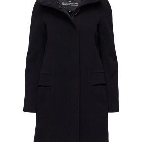 Frakken er købt i 2017, da jeg stod og skulle til Grønland. Denne er den perfekte kombination af både meget varm og pæn på samme tid. På andet billede ses hvad frakken er lavet af.