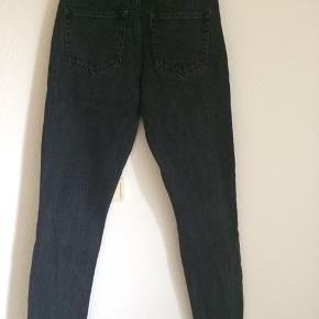 """Lækre jeans i tykt sort denim fra Monki.  Det er modellen """"High relaxed"""" og de er derfor meget højtaljede og sidder rigtig flot.  Der er et hul under en af bæltestropperne bagpå (se billede), men det er ikke noget, der er meget tydeligt."""