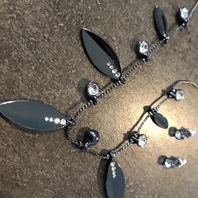 Varetype: Smykkesæt Størrelse: - Farve: Mørk Grå  Smukt smykkesæt med øreringe og halskæde. Brugt en gang.