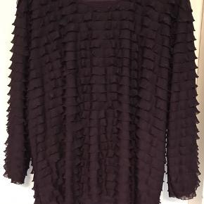 Bluse med masser af stræk. Mærket er 'Bassini'. 3/4 ærmer. 92% polyester og 8% elastan. Brystvidde: 73 cm. X 2. Længde: 75 cm.