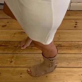 Lækre beige læder sandaler i gladiator stil, i virkelig go kvalitet. Guld spænder langs siden der kan spændes i 3 forskellige størrelser, og lynlås på indersiden så du nemt kan få dem af og på. Det er str 38, men jeg bruger 37 normalt og de passer mig helt perfekt.