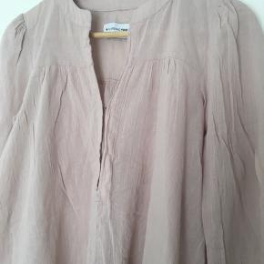 Fin bluse i støvet rosa str. XS. Bred model som også kan passes af str. S. Stumpeærmer og holdes sammen foran med to hægter. Brugt men pæn uden huller eller pletter eller slid.