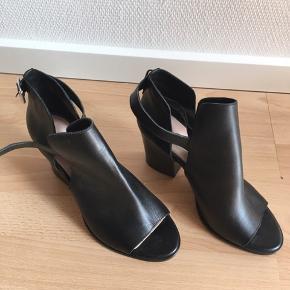 Sort læder højhælet str 42,  normal i str. Hæl 8,5cm. Utrolig lækre at have på. Åben ved tæerne og i siderne. Lukkes med rem. Np 700kr Aldrig brugt Har stået pænt på sko hylden i et år