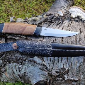Unika jagtkniv til den kvalitetsbevidste jæger. Skæftet er lavet af eukalyptus træ (Australien) med bøffelhorn, samt tin indlæg. Klinge af Per Glerup. Skeden er lavet af hårdpresset læder, sort farvet og efterfølgende præget.  Alt er håndlavet med fokus på detalje og super finish af erfaren knivmager. Spørg evt efter flere detaljer og billeder.