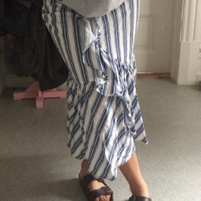 Smart Midi-nederdel fra MUNTHE fremstillet i kraftigt blåt- og hvidstribet materiale. Slank silhuet med høj talje og lynlås i siden. Nederdelen har en bred flæse fra taljen og hele vejen rundt forneden. Kan styles sammen med en striktrøje og støvletter og på varme dage med sandaler og en top.  Farve: BLÅ Kvalitet: 87% Tencel, 13% Hør Vask: Håndvask Anbefales  Sælges til højst bydende, åben for bud!
